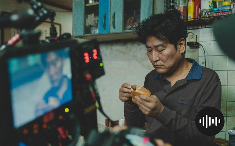 Na imagem, em primeiro plano está a câmera de captação da cena, e no segundo plano, um dos personagens do filme está sentado preparando um sanduíche em uma cozinha que demonstra um cenário vulnerável.